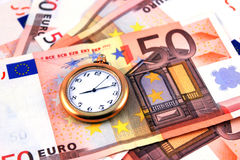 Time and money. Old hours with arrows against euro money Stock Photo