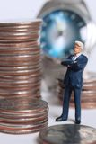 Time is money. Man standing with money and time on background Royalty Free Stock Photo