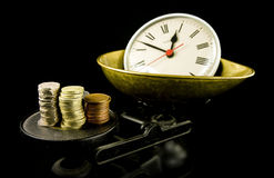 Time is money. Clock and money on scales Stock Photos