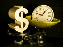 Time is money. A gold dollar sign and a clock on scales Stock Photography