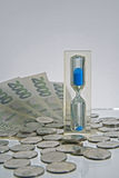 Time is money. Hourglass with blue sand and banknotes and coins Royalty Free Stock Photo