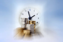 Time is money. Abstract time is money with blured clock and  coins concept Royalty Free Stock Images