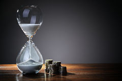Time is money. Deadline and time is money concept with hourglass and British coin currency