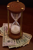 Time is money. Concept of an hour glass with time passing over money Stock Photos