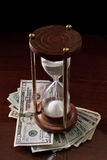 Time in money. Concept of an hour glass with time passing over money Stock Photos