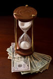 Time in money. Concept of an hour glass with time passing over money Royalty Free Stock Photos