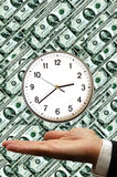 Time is money. Businessman hand with a clock floating above and a dollar banknotes background Royalty Free Stock Photography