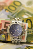 Time is money. The time is of utmost importance in business. A roll of euro bills bound by wristwatch royalty free stock photography