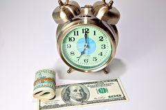 Time is Money 4. Old fashioned alarm clock with stack of 100 dollar bills isolated on white background Royalty Free Stock Photo