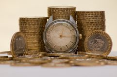 Time is a money. Ancient watch against a coins Stock Photos