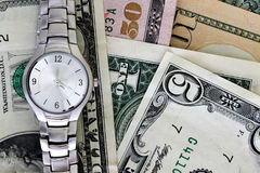 Time and money. A silver watch lying on dollar bills Royalty Free Stock Photography