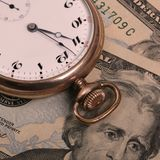 Time is Money. Old Style Pocket Watch on top of US Currency Stock Images