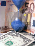 Time is money. Dollars and euro with a hourglass stock photo