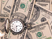 Time & money. A pocket watch on a variety of US currency Stock Images