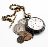 Time is money. Watch with small chain and coins on white isolated stock image