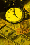 Time is money. Clock standing on different banknotes royalty free stock photos