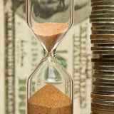 Time - money. Hourglass on the background money Royalty Free Stock Photo