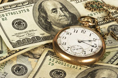 Time is Money. 1800's railroad pocket watch sitting on a stack of U.S. cash reflecting time and money Stock Photo