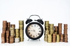 Time and money abstraction. A lot of coins with elegant black clock stock image