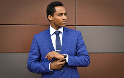 Time is money. Successful businessman expects a meeting of shareholders. African important, handsome, young person, happy businessman, worker corrects hours on stock photography