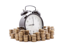 Time is money. Alarm clock with stacks of coins. Royalty Free Stock Image