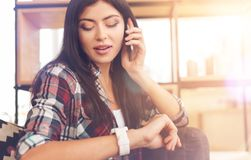 Busy young lady checking time while talking on phone. Time is money. Beautiful brunette wearing casual attire looking at a wrist watch for time checking while Stock Photos