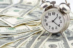 Time - money. Business concept. Analog hours on a heap of paper dollars Stock Images