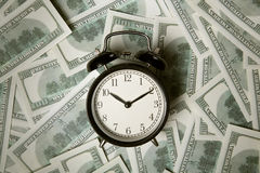 Time - money. Business concept. Analog hours on a heap of paper Stock Photos