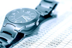 Time Is Money. Business concept. Closeup of wristwatch on paper background with digits Royalty Free Stock Photography