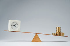 Time is money. Clock and money coins stack balancing on a seesaw Royalty Free Stock Photography