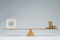 Time is money. Clock and money coins stack balancing on a seesaw Stock Photos
