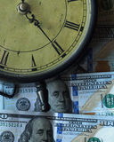 Time and Money. A clock and money, $100, one-hundred dollar bills Stock Image