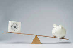 Time is money. Clock and piggy bank balancing on a seesaw Royalty Free Stock Image