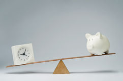 Time is money. Clock and piggy bank balancing on a seesaw Stock Photography
