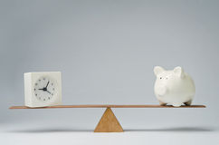 Time is money. Clock and piggy bank balancing on a seesaw Royalty Free Stock Photo