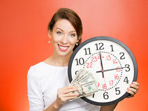 Time is money. Closeup portrait happy young business woman, corporate employee, ceo holding wall clock, dollar bills in hands. Time is money concept isolated red royalty free stock photography