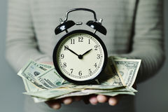 Time is money. Closeup of a young caucasian man with an alarm clock and many US dollar banknotes in his hands, depicting the idea that time is money stock image