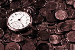 Time And Money Concept. A business concept image portraying time and money. An old pocket-watch and US coins Royalty Free Stock Photos