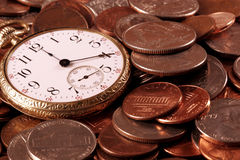Time And Money Concept. An old pocket watch atop US coins Stock Photography