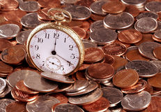 Time And Money Concept. A concept image of an old pocket-watch and US coins Royalty Free Stock Images