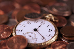 Time And Money Concept. A concept image for business investment and strategy. An old pocket-watch and US coins Stock Photo