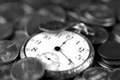 Time And Money Concept. A black and white image of time and money. An old pocket-watch and US coins Royalty Free Stock Photo