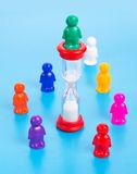 Time is money concept. Colorful toy people standing in a circle around sandclock Stock Photo