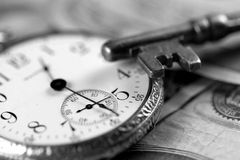 Time And Money Concept. A portrayal of business success concepts with skeleton key, watch and US currency. Black and white image Royalty Free Stock Image