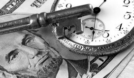 Time And Money Concept. A portrayal of business success concepts with skeleton key, watch and US currency royalty free stock images