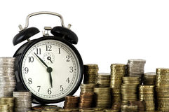TIME IS MONEY concept: alarm clock and euro coins. Alarm clock standing with coins on metal plate stock photo