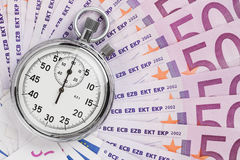Time is money. Concept, analog stopwatch on the euro banknotes Royalty Free Stock Image