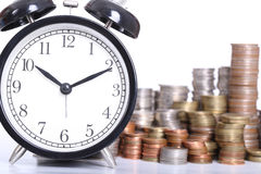 Time is Money concept with clock and coins stack Stock Images