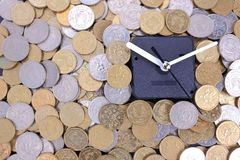 Time is money. Concept . A clock is surrounded by gold and silver coins Royalty Free Stock Photo