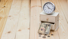 Time and money concept. Clock and wood box with money Stock Photo